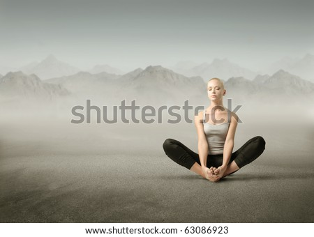 Beautiful woman meditating on a mountain - stock photo