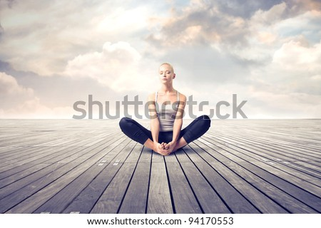 Beautiful woman meditating on a parquet floor - stock photo