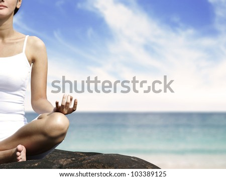 Beautiful woman meditating on the beach sitting over a stone