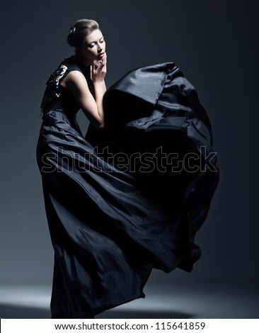 beautiful woman model dressed in an elegant long blueish black dress in a fashion pose - stock photo