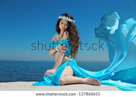 Beautiful woman model in Blowing Dress Flying resting over blue sky - stock photo