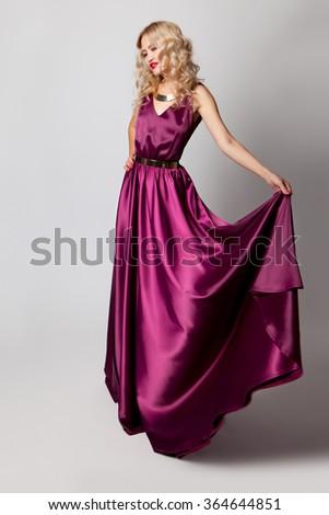 Beautiful woman model posing in elegant purple silk dress in the studio - stock photo
