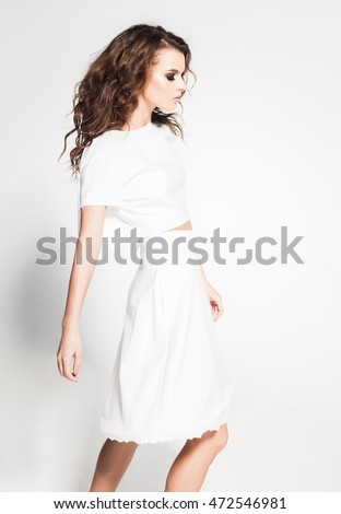 beautiful woman model posing in white dress in the studio