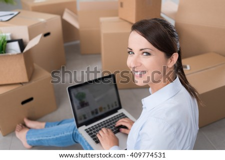 Beautiful woman moving in her new house and unpacking, she is sitting on the floor surrounded by boxes, using a laptop and smiling at camera - stock photo