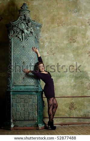 Beautiful woman near a fireplace with patterns in an old house