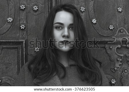 Beautiful woman near an old door. Black and white shot