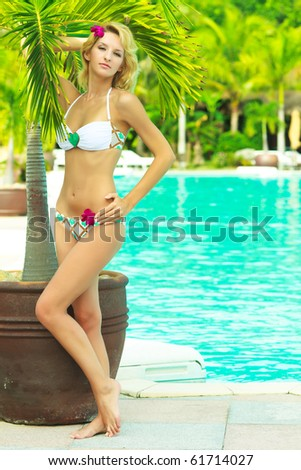 Beautiful woman near swimming pool under palm tree - stock photo