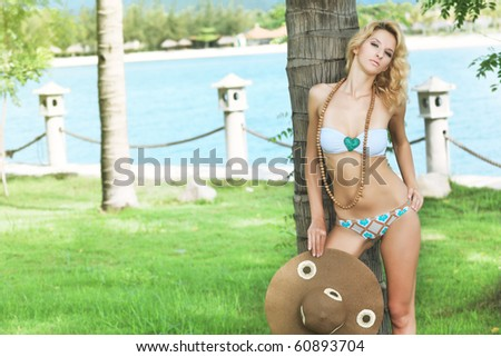 Beautiful woman near the trunk of palm tree - stock photo
