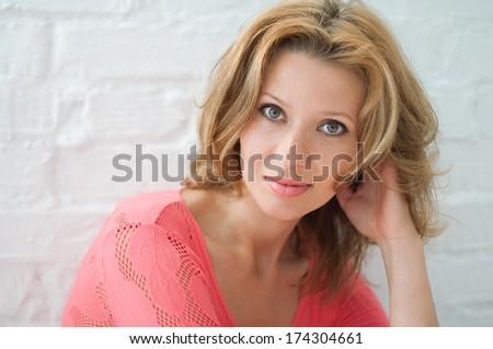 Beautiful woman near the white brick wall - stock photo