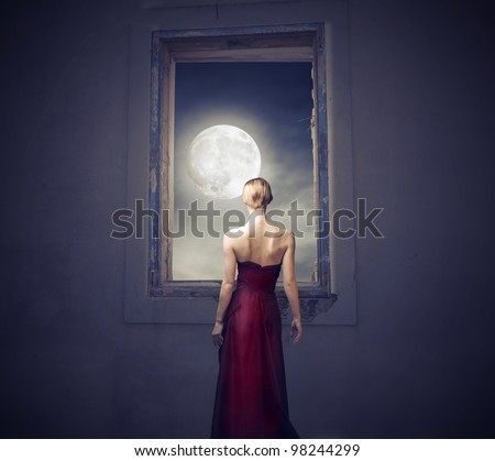 Beautiful woman observing the moon from a window [elements of this image furnished by NASA] - stock photo