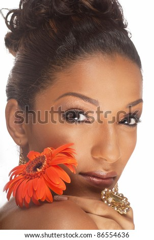 Beautiful woman of East Indian ancestry looking over her shoulder with a beautiful flower