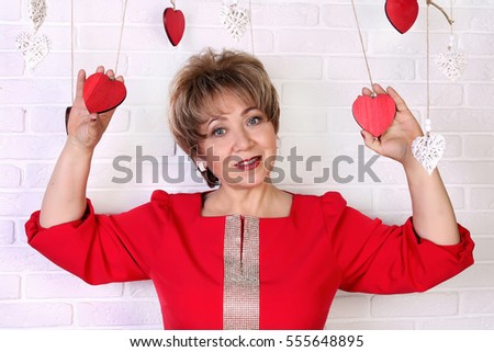 Beautiful woman of 50 years in red dress holds in hands hearts