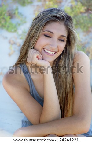 Beautiful woman on a beach on a sunny day sitting on the sand