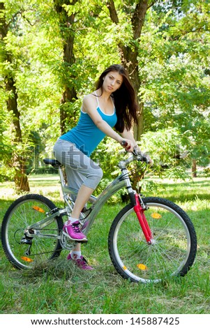 Beautiful woman on a bicycle in the forest at full height - stock photo