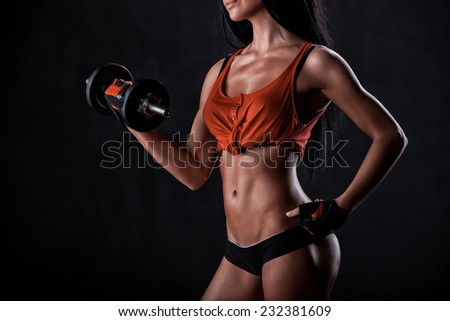 beautiful woman on a dark background is engaged in fitness - stock photo