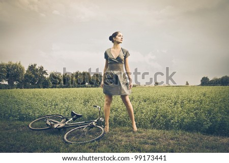 Beautiful woman on a green meadow with bicycle beside her - stock photo