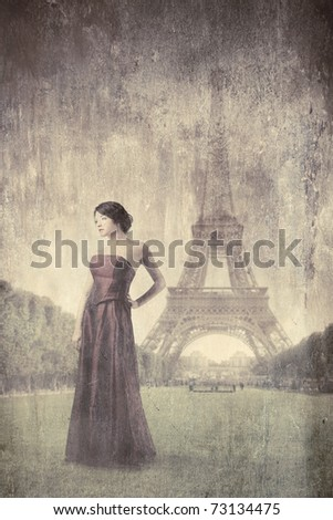 Beautiful woman on a green meadow with Eiffel Tower on the background - stock photo