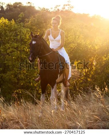 Beautiful woman on a horse. Horseback rider - stock photo