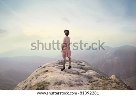 Beautiful woman on a peak over the mountains
