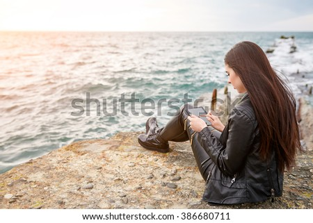 Beautiful woman on a pier working with the tablet