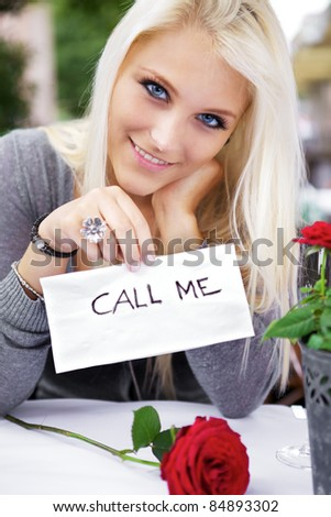 Beautiful woman on a restaurant wrote a 'call me' note on a napkin. - stock photo