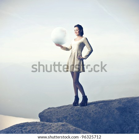 Beautiful woman on a rock over a lake holding a crystal ball - stock photo