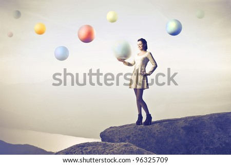 Beautiful woman on a rock over a lake holding a crystal ball with other spheres in the background - stock photo