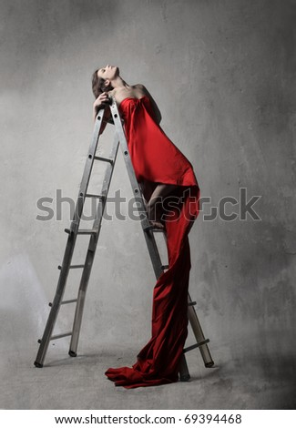 Beautiful woman on a scale with very long dress - stock photo
