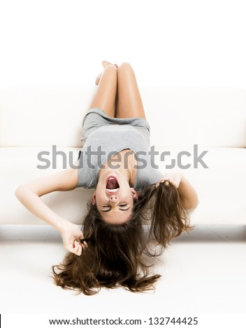 Beautiful woman on a sofa with head upside down and yelling, isolated in white - stock photo