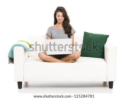 Beautiful woman on a sofa working with a laptop, isolated in white - stock photo
