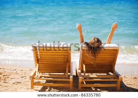 beautiful woman on a tropical beach on a chaise lounge - stock photo