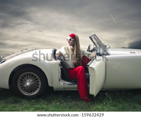 beautiful woman on a vintage car - stock photo