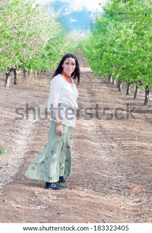Beautiful woman on a walk among the first leaves in a spring alley