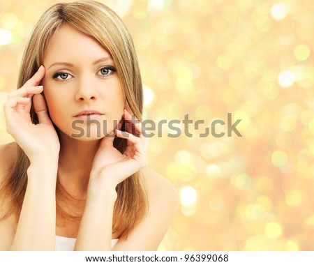 Beautiful woman on abstract golden background - stock photo