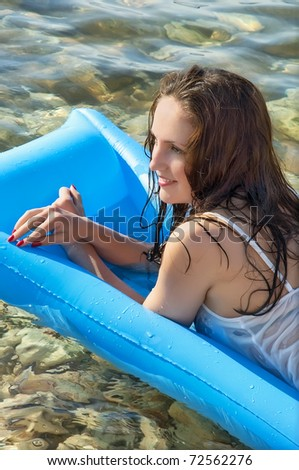 beautiful  woman on an air mattress on the sea - stock photo