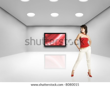 Beautiful woman on big room with a big TV - stock photo