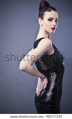 Beautiful woman on black classical dress pose in studio. Vogue style photo.