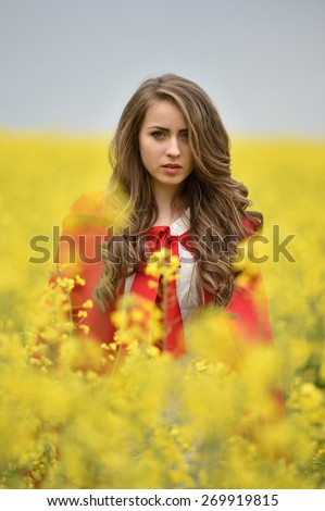beautiful woman on blooming rapeseed field in spring - stock photo