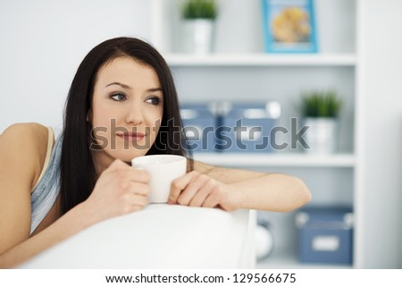 Beautiful woman on couch with cup of coffee - stock photo