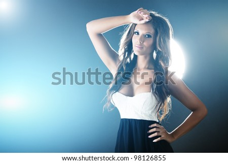 Beautiful woman on dark background with blue lights - stock photo
