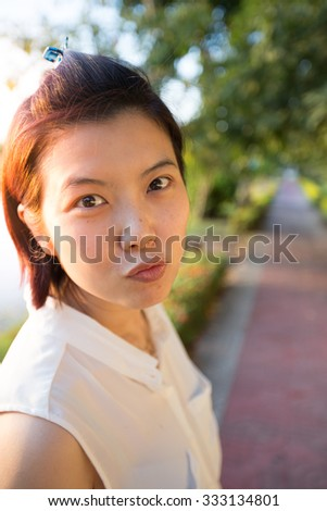 Beautiful woman on footpath in the garden. Portrait asian woman in emotion