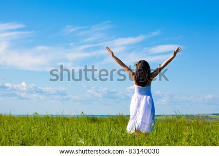 beautiful woman on green field wearing white dress - stock photo