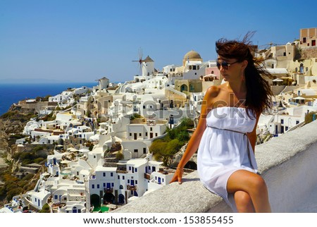 Beautiful woman on holidays, Santorini. Oia town view - stock photo