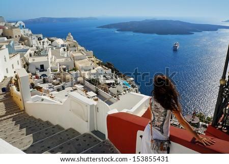 Beautiful woman on holidays, Santorini Thira town view - stock photo