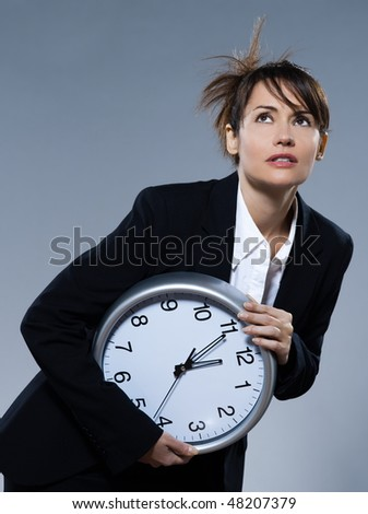 beautiful woman on isolated backgound holding a clock - stock photo