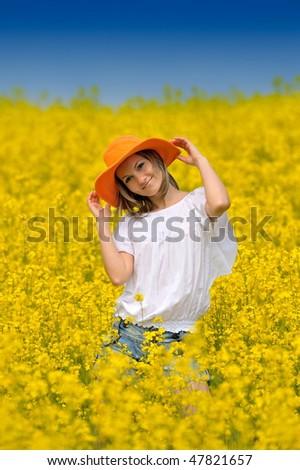 beautiful woman on rapeseed field in bloom - stock photo