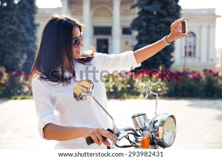 Beautiful woman on scooter making selfie photo on smartphone in old european town - stock photo