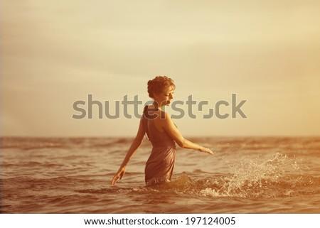 Beautiful woman on the beach at sunset. - stock photo