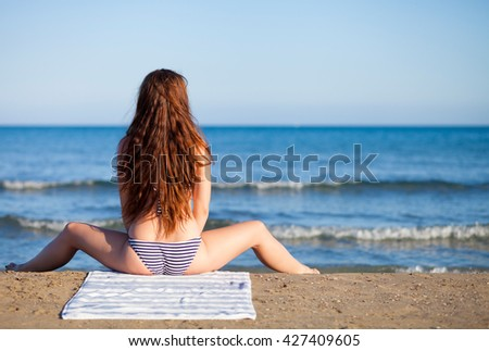 Beautiful woman on the beach during summer vacation, back view - stock photo