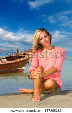 Beautiful woman on the beach in Thailand with long tailed boat on background - stock photo